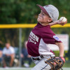 A Little League pitcher delivers during a game