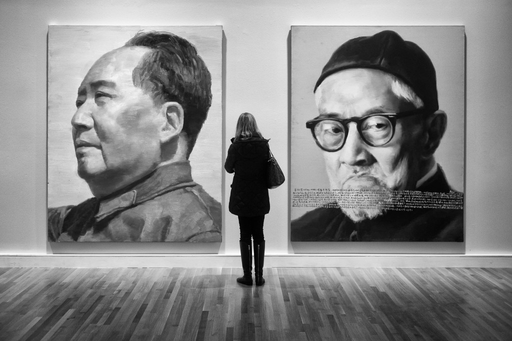 A woman looks at two large paintings